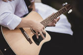 Hands of wedding groom playing the guittar — Stock Photo