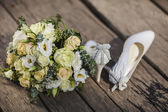 Wedding flowers bouquet and bride shoes — Stock Photo