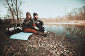 Hikers sitting on the lake shore — Stock Photo