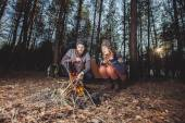 Couple of hikers starting a fire in the wood — Stock Photo