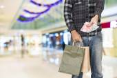 Exciting young shopping man hold bags, closeup portrait with copyspace. — Stockfoto
