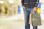 Exciting young shopping man hold bags, closeup portrait with copyspace. — Zdjęcie stockowe