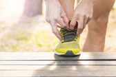 Sport, fitness, exercise and lifestyle concept - runner man lacing trainers shoes — Stock Photo