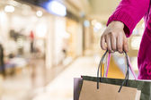 Exciting young shopping woman hold bags, closeup portrait with copyspace. — Stock Photo