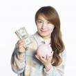 Young female student holding a piggy bank with dollars, concept of savings — Stock Photo #64282987
