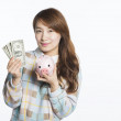 Young female student holding a piggy bank with dollars, concept of savings — Stock Photo #64283001