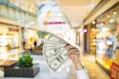 Holding dollars in the mall background — Stock Photo