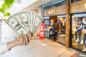 Dollar halten im Einkaufszentrum Hintergrund — Stockfoto