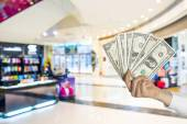 Holding dollars in the mall background — Stockfoto