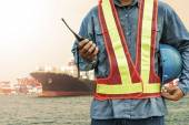Harbor dock worker talking on radio with ship background — Stockfoto