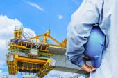 Construction worker checking location site with crane on the background — Stock Photo