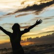 Woman open arms under the sunrise at seaside — Stock Photo #76004921