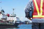 Harbor dock worker talking on radio with ship background — Stock Photo