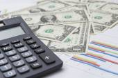 Analyzing financial data on digital tablet and counting on calculator — Stock Photo