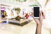 Utilizzando smartphone in un negozio di mercato o di reparto, closeup immagine. — Foto Stock