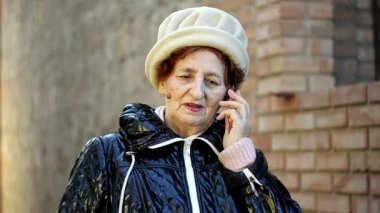 Senior woman making a phone call with her mobile phone outdoor — Vídeo de stock