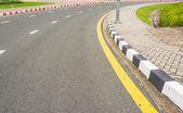 Asfalt silniční textury s žlutým pruhem — Stock fotografie