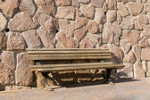Old bench on stone wall background — Stockfoto