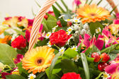 Bouquet of multi-colored flowers in a wattled basket — Stock Photo