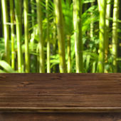 Green bamboo grove background with wooden table — Stock Photo