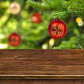 Wooden table on red Christmas ball background — Stock Photo