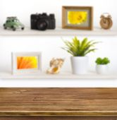 Wooden table on background of shelves with travel objects — Stock Photo
