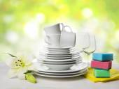 Clean tableware, dishwashing sponges and lily flower over abstract background — Stock Photo