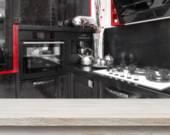 Beige table on defocused black kitchen background — Stock Photo