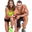 Beautiful young sporty couple posing and showing muscle — Stock Photo #55008301