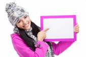Smiling girl pointing at a blank board isolated — Stock Photo