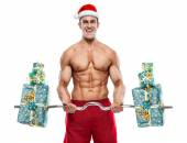 Muscular Santa Claus doing exercises with gifts over white backg — Stockfoto