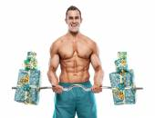 Muscular bodybuilder guy doing exercises with gifts over white b — Stock Photo
