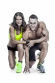 Beautiful young sporty couple posing and showing muscle — Stock Photo