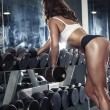 Nice sexy woman doing workout with dumbbells — Stock Photo #74888697
