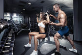 Beautiful young sporty sexy couple in gym — Stock Photo