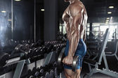 Muscular bodybuilder guy doing exercises with big dumbbell — Stock Photo