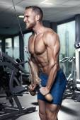 Muscular bodybuilder guy doing triceps exercises — Stock Photo