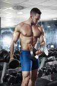 Muscular bodybuilder guy doing exercises with dumbbells — Stock Photo