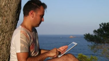 Browsing Tablet Next to the Sea — Stock Video