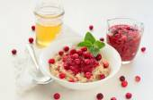 Oatmeal with cranberry jam, fresh cranberries and honey — Stock Photo
