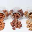 Hazelnut , almond and walnut in glass jars on white wooden background. — Stock Photo #65382937