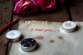 """Rose and a note with the text """"I love you"""" on a wooden background.Spilled wax from a dead candle. — Stock Photo"""