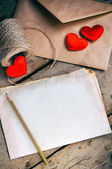 Old white sheet of paper and a pencil on a wooden background.The envelope,coil of twine and  little red hearts. — ストック写真