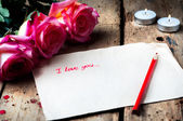 """Rose and a note with the text """"I love you"""" on a wooden background.Two small candles. — Stock Photo"""