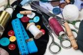 Sewing kit with scissors, spools of thread and needles on white wooden background. — Stock Photo