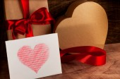 Gifts wrapped with a red ribbon and cardboard heart..White card with a red heart.Valentine's day. — Stock Photo