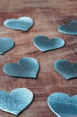 Silver cardboard hearts on a brown wooden background. — Stock Photo