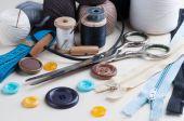 Sy-kit med sax, knappar, spolar med tråd och nålar på vit trä bakgrund. — Stockfoto