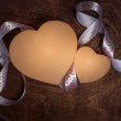 Valentine's day.Two cardboard hearts and white ribbon on a wooden brown background. — Stock Photo #65585649