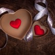 Valentine's day.Two cardboard hearts with red hearts inside and white ribbon on a wooden brown background. — Stock Photo #65585675